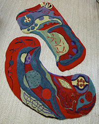 two interlocking textured kidney shaped rugs in red and teal organic shapes